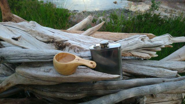 A hip flask and a wooden drinking cup on some driftwood. The hip flask contains excellent moonshine!